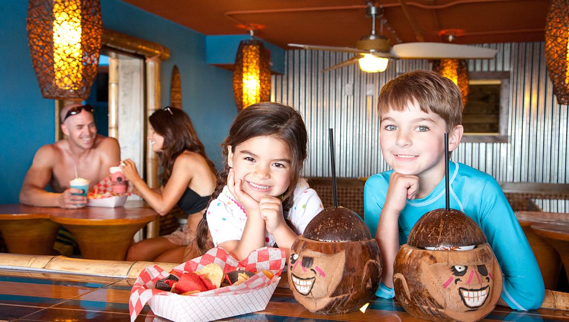 Kids enjoying drinks in a coconut