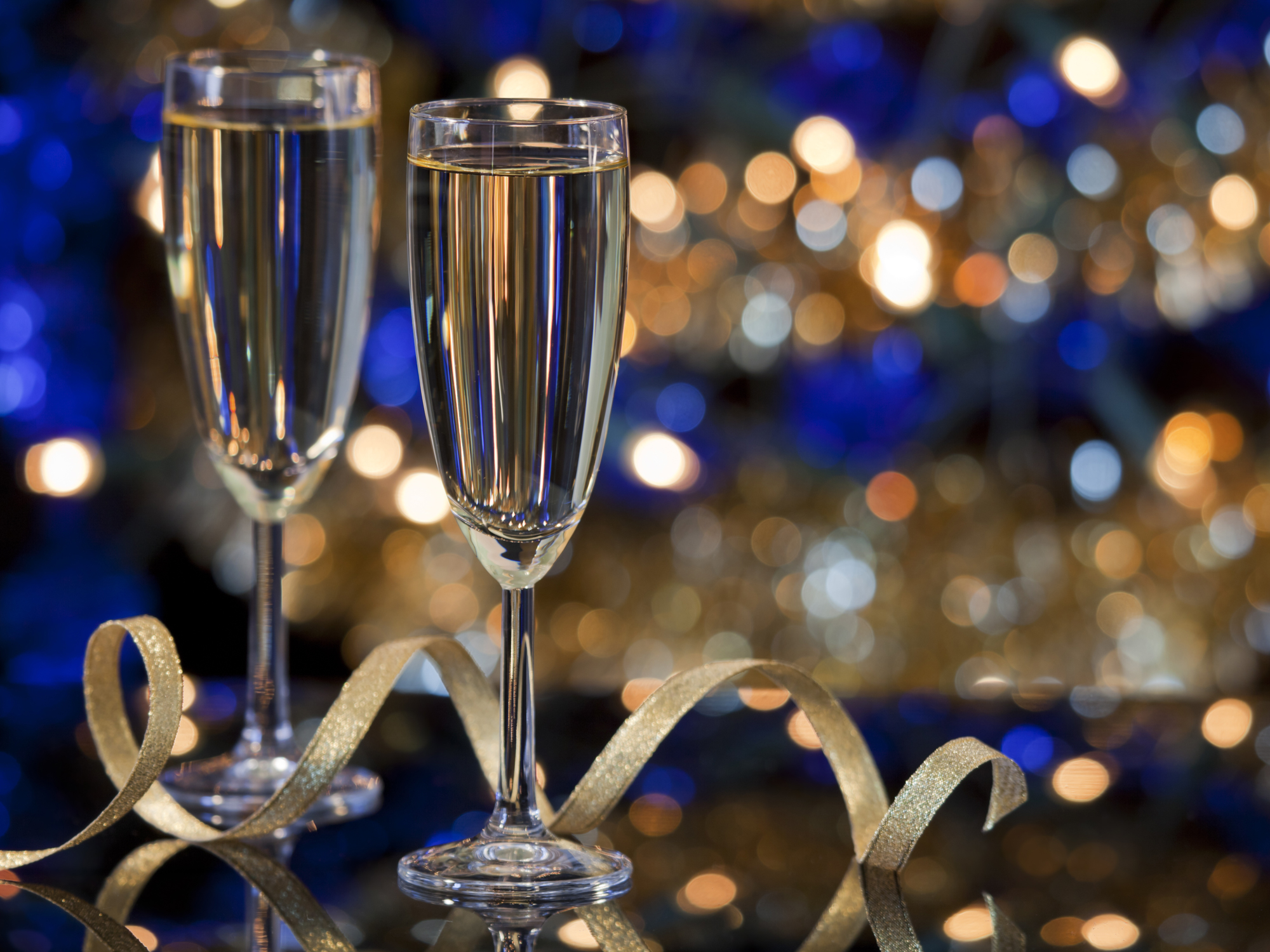 champagne glasses against blue and gold background